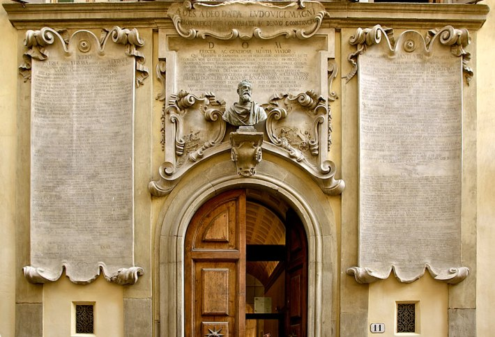 Palazzo dei Cartelloni, facade detail of the scrolls and bust of Galileo