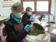 SACI students Ariel Scotti and Liah Spilove carefully do the delicate and precise work required for cleaning the ancient metal.