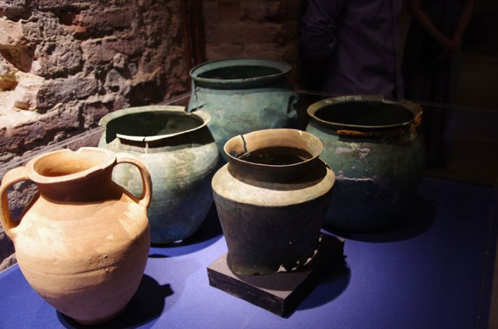 Three Roman and one Etruscan bronze situla (bucket) and a terracotta wine amphora on display