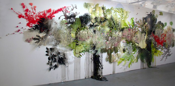 """Resa Blatman: """"Gaia,"""" part 1, 2014 (ongoing) Oil and glitter on laser-cut Mylar, PVC, and PETG; oil and latex paint on hand-cut Mylar; silk and plastic flora, 360w x 120h x 12d inches"""