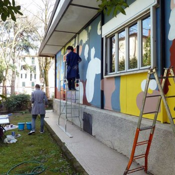 SACI student, John Gingrich painting a mural project at Fili e Colori in Florence